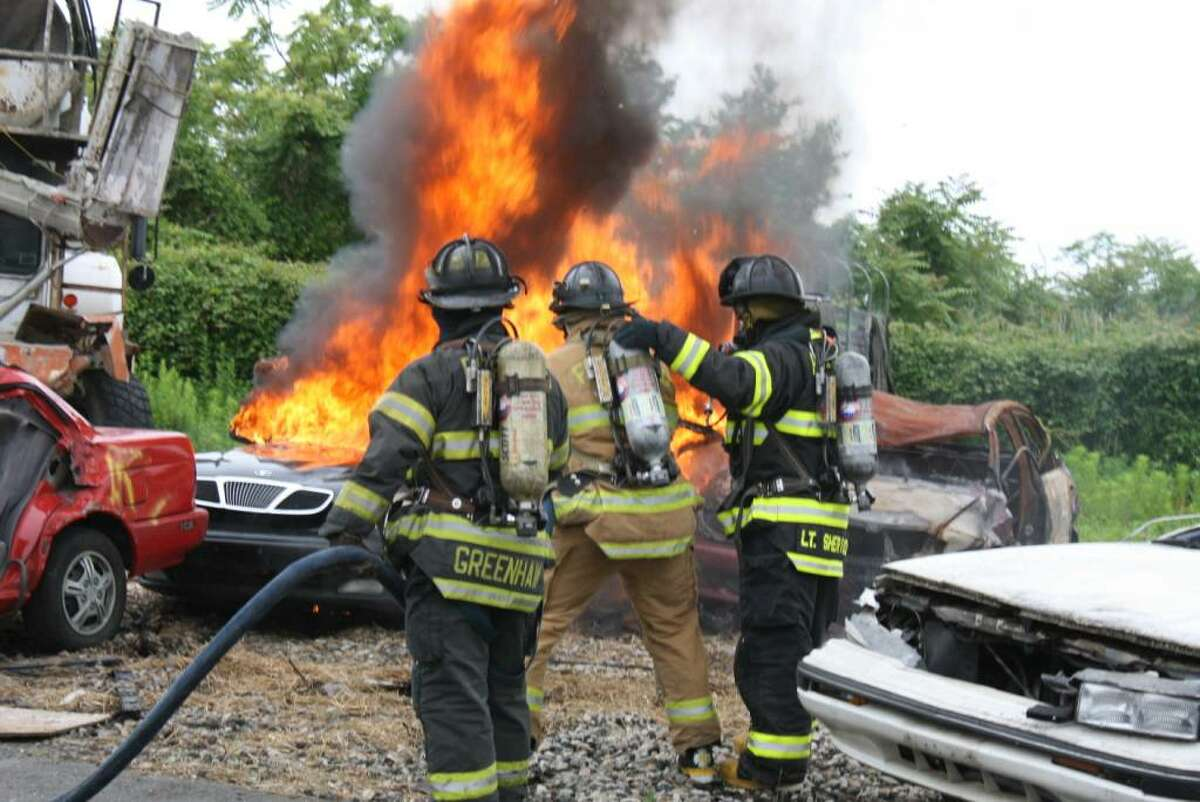 Anthony Wadelton, center, a Fairfield Ludlowe High School senior, battles a car fire at the Fairfield Fire Training Center as part of his internship with the Fire Department. He is supervised by Firefighters Sherwood and Greenhaw.