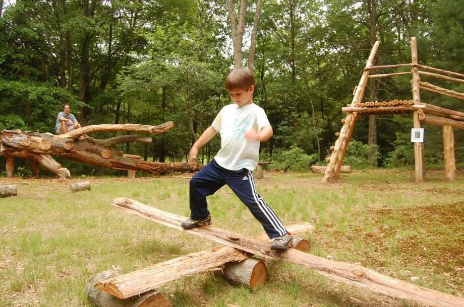 Jack Huber, 6, balances on a seesaw at the new natural playground at the Leonard Schine Nature Preserve on Glenndinning place off of Weston Road. His father, Ted, watches in the background. Photo: Anthony Karge / Westport News