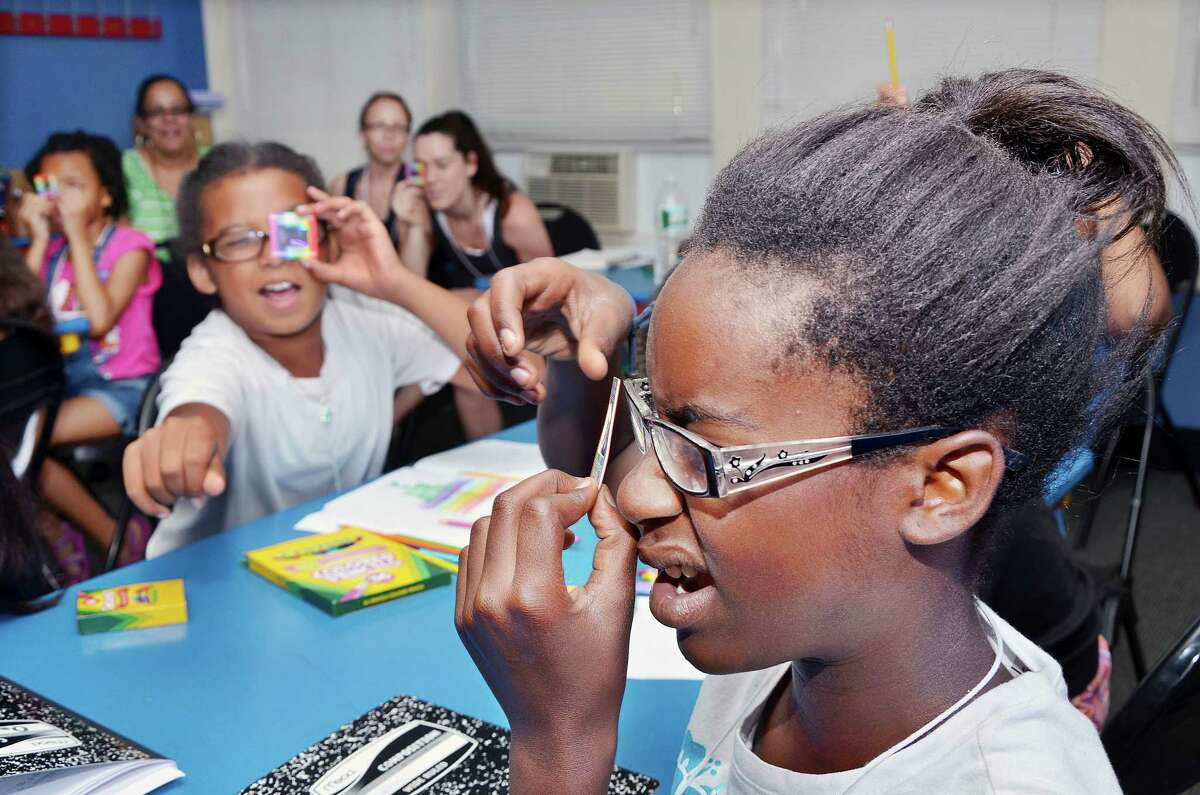 August 6, 2014 - Tyshala Morris-Hayes, 11, at right and Julia Martinez, 10 react to using a linear diffraction grating to see scattered red laser light during a class taught by Wesleyan physics professor Christina Othon at the Girls in Science Summer Camp at Green Street Arts Center. Wesleyan faculty and students taught ten girls about mutations, light, color, DNA, gardens, insects, created germ plates, designed a bacteria in the art room through out the week. (Catherine Avalone/The Middletown Press)