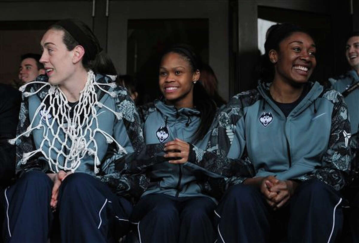 Connecticut's Breanna Stewart, left, Moriah Jefferson, center, and Morgan Tuck, right, sit during a rally on campus to celebrate their team's 10th national title and third in a row, Wednesday, April 8, 2015, in Storrs, Conn.