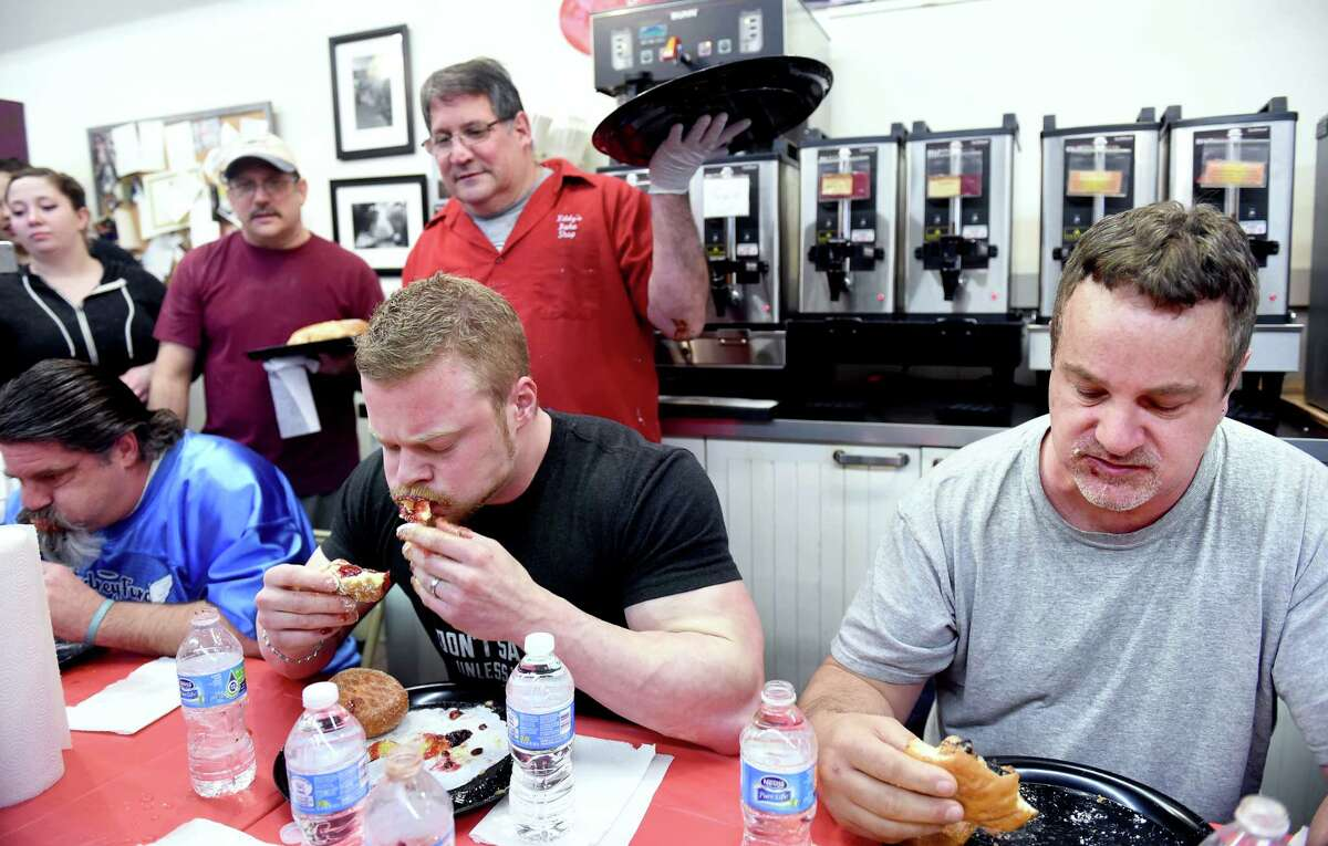 Paul Ciocca (top center), owner of Eddy's Bake Shop, watches Nick Wehry (bottom center) of Torrington finish his ninth paczki to win the 19th annual paczki eating contest in Ansonia on 2/28/2017. At right is Lorenzo Manware of West Haven. Photo by Arnold Gold/New Haven Register agold@newhavenregister.com
