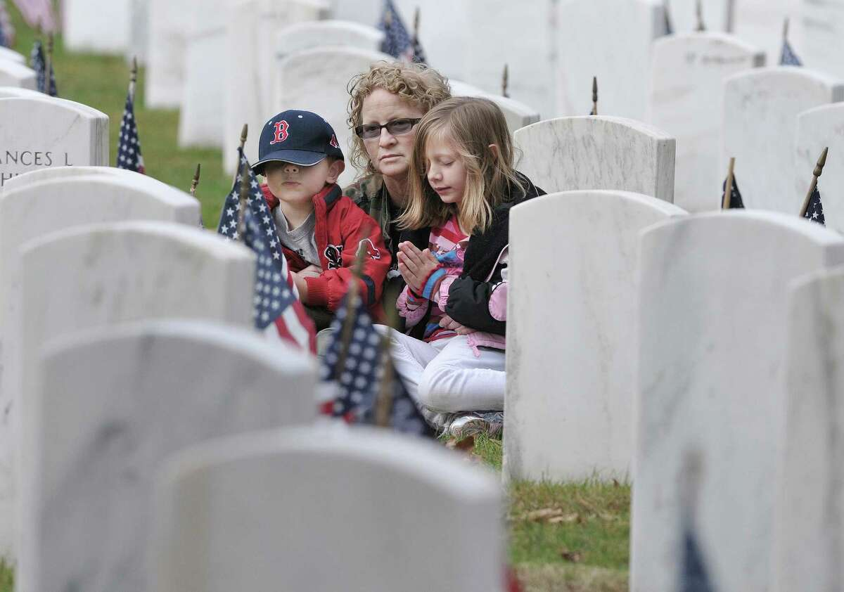 Hamden resident Marie Perkins visits her father's grave, Albert J. Perkins, a SFC in the US Army and Navy, who served in both Korea and Vietnam. Perkins is visiting with her 7-year-old granddaughter Nyla Campaniolo and 4-year-old grandson Aidan Campaniolo. Nyla said,