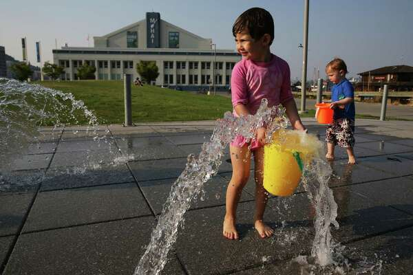 Skye Yen-Ladd, 3, and Ethan Davis, 2, fill buckets with water in the fountains in Lake Union park as temperatures rise, Wednesday, Aug. 1, 2017.