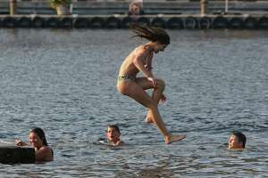 Teens swim in Lake Union at Lake Union Park as temperatures rise, Wednesday, Aug. 1, 2017.