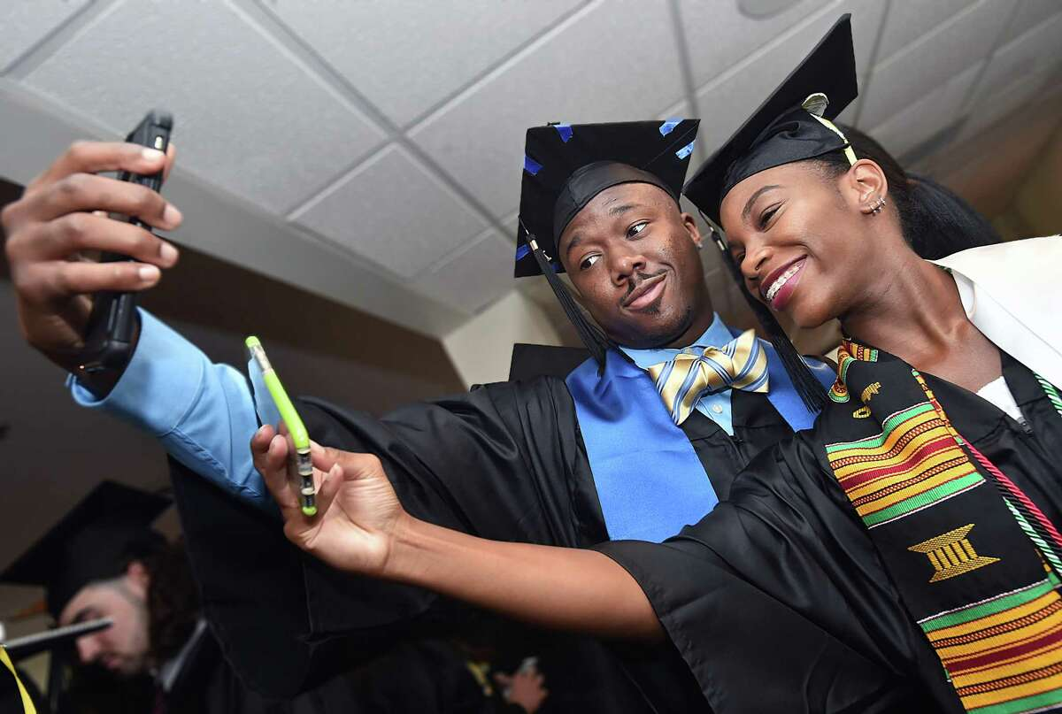 Rishawn Harris, of Springfield, Massachusetts and Taylor Stewart-Grant, of Bronx, New York take a dual selfie at the University of New Haven commencement exercises for the College of Business and the Henry C. Lee College of Criminal Justice and Forensic Sciences, Saturday, May 13, 2017, at the Toyota Presents Oakdale Theatre at 95 South Turnpike Road in Wallingford. Harrisreceived a Bachelor of Science in sports management and Stewart-Grant received a BS in accounting. (Catherine Avalone - New Haven Register)