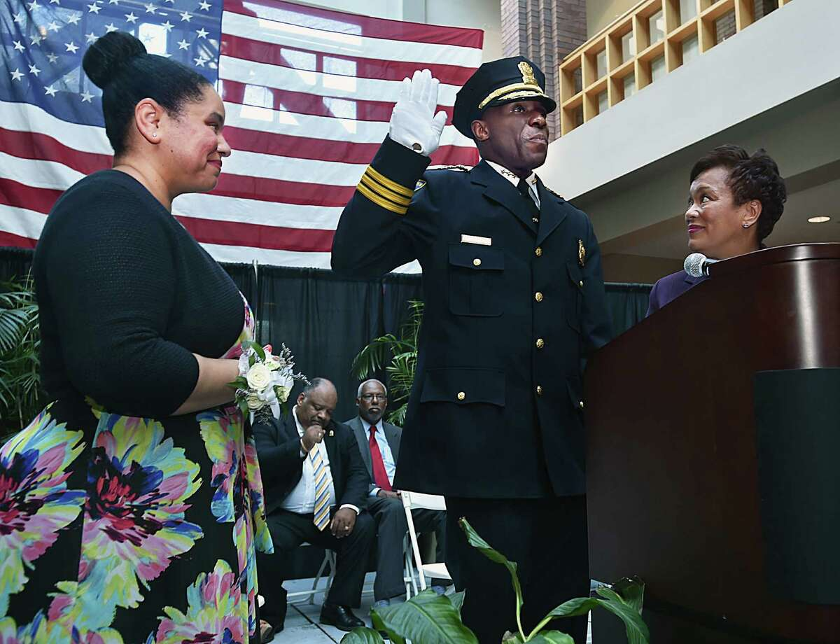 Mayor Toni Harp swears in Anthony Campbell, as the chief of the New Haven Police Department, Tuesday, June 20, 2017, at the First Floor Atrium at New Haven City Hall. Stephanie Campbell, at left, pinned the badge on her husband on their wedding anniversary shortly before taking the oath of office. The Campbells have three sons, Graham, 15, Sander, 13 and Paxon, 8. (Catherine Avalone / Hearst Connecticut Media)