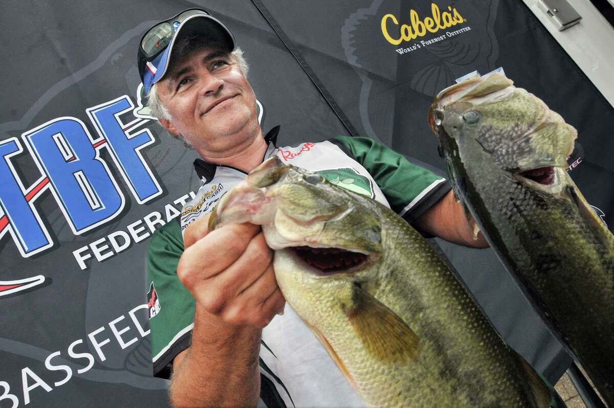 Newington angler Dino Moutogiannis, formerly of Middletown holds two of the five large mouth bass Friday afternoon shortly before winning the The Bass Federation Eastern Division Championship at Harbor Park in Middletown. Moutogiannis has been fishing the Connecticut River for 25 years. Moutogiannis reeled in 15 fish during the three day competition weighing 30 lbs. and 8 ozs. Moutogiannis, a member of the Connecticut State Team of The Bass Federation and his teammates caught 196 lbs.10 ozs., a 117 fish in total to clinch first place. Catherine Avalone - The Middletown Press