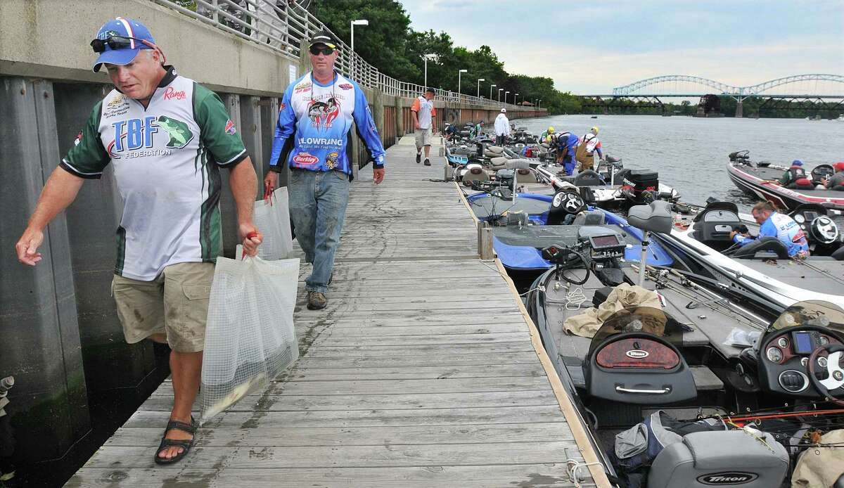 Westbrook angler Ken Bugden, at left and John Ahern, of Ashaway, Rhode Island carry their day's catch to the running bump station at Harbor Park to get counted and weighed Friday afternoon. Bugden, a member of the Connecticut State Team placed 16th overall and Ahern came in 20th in The Bass Federation Eastern Division Championship on the Connecticut River in Middletown. Catherine Avalone - The Middletown Press