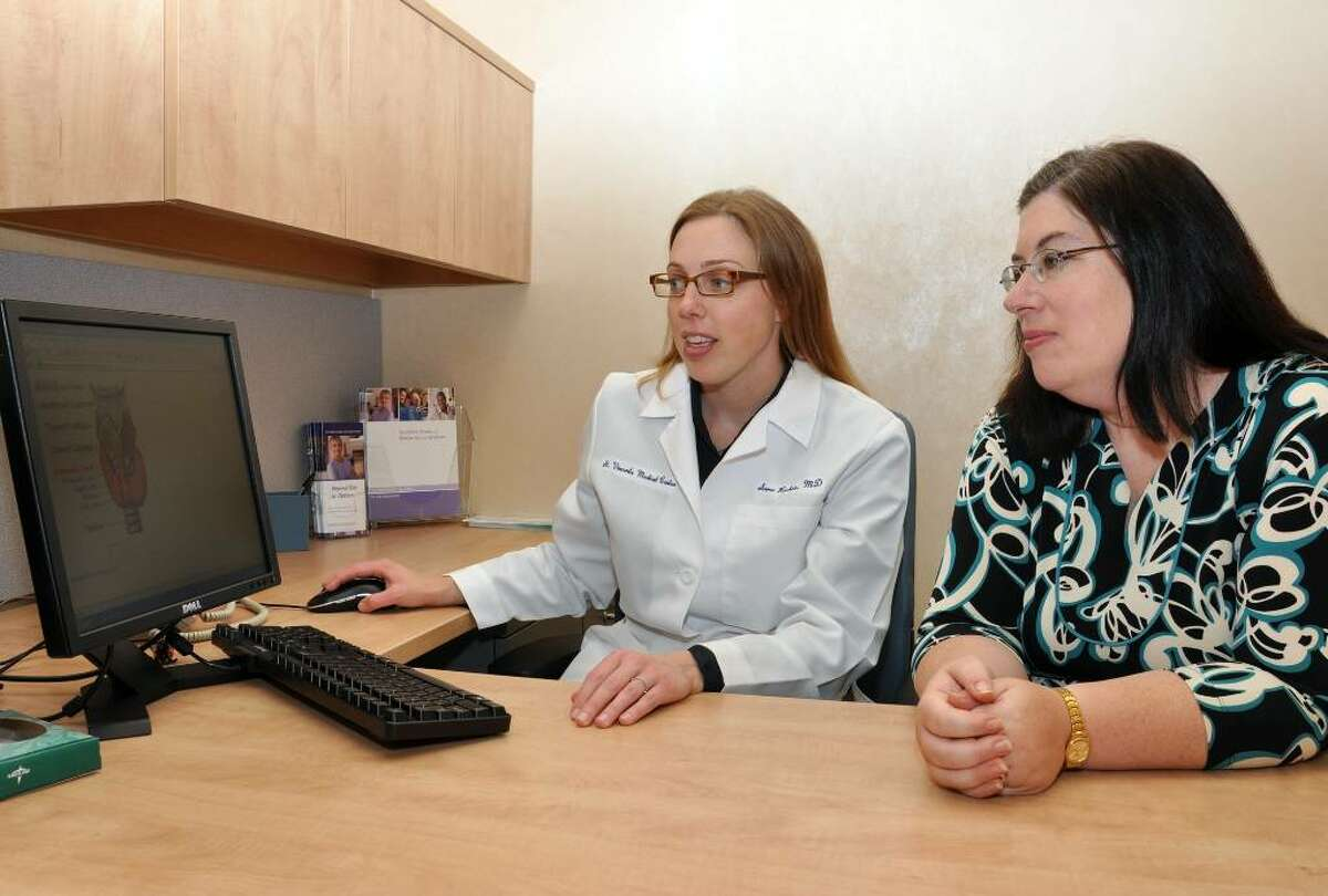 Dr. Sara Richer, endocrinologist, shows her patient, Laura Longueira, of Fairfield, a diagram of a thyroid at St. Vincent's Hospital on Friday, June 4, 2010.