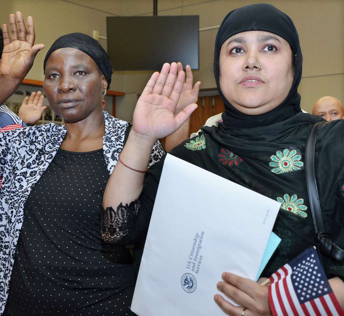 July 2, 2014 - New citizens, Bridgeport resident Amina Begum, of Bangladesh, at right and New Haven resident Zainab Ahmed Saido, of Nigeria raise their right hand as Judge Stefan Underhill administers the Oath of Allegiance at the Naturalization Ceremony at Middletown City Hall Wednesday afternoon. (Catherine Avalone/The Middletown Press)