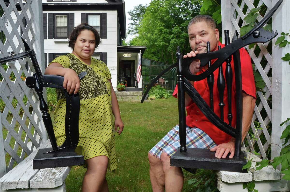 July 2, 2014 - Artists Gary O'Neil and his daughter, Kyle, 28 at their East Hampton home Wednesday afternoon with two of Gary's wood sculptures made from furniture parts. (Catherine Avalone/The Middletown Press)
