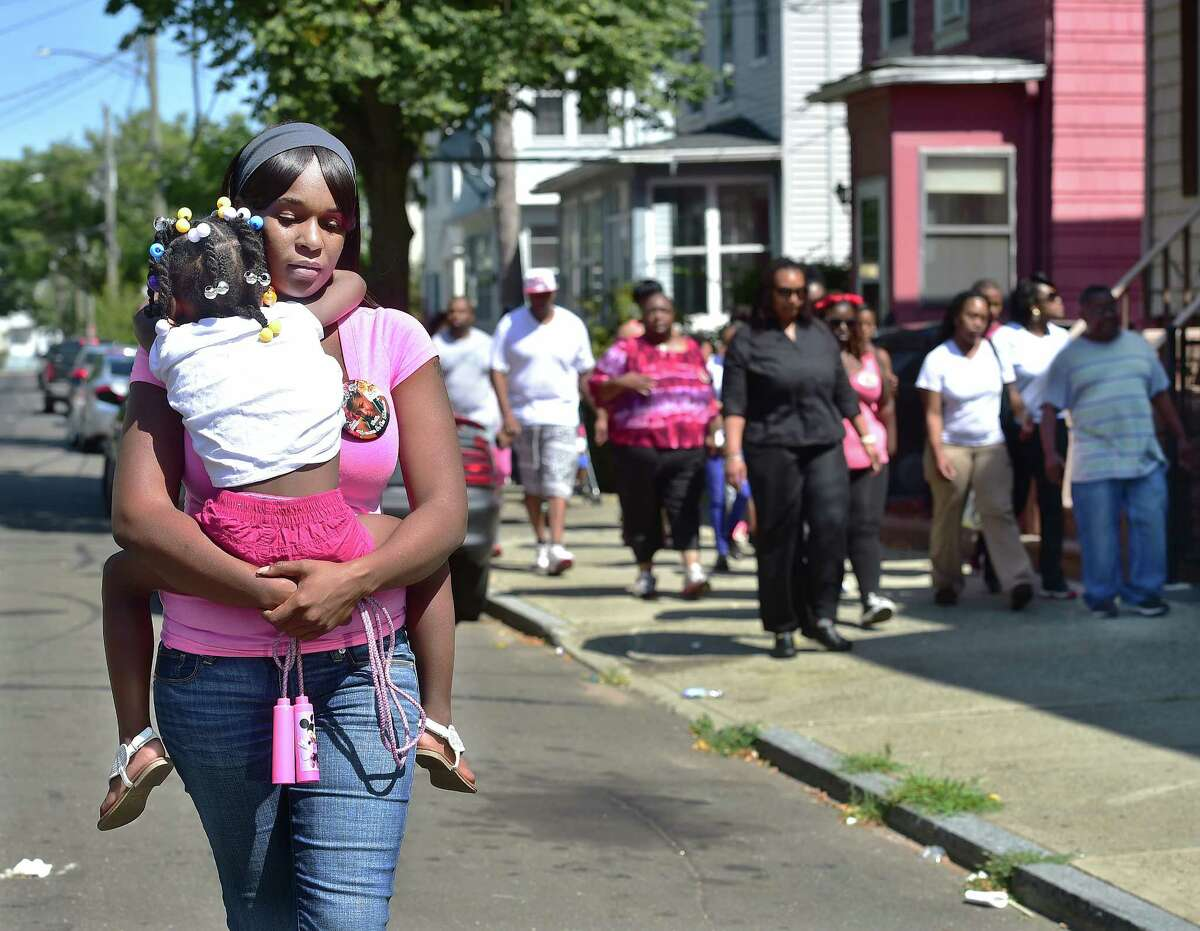 (Catherine Avalone - New Haven Register) Shante Howard carries her four-year-old neice Chawnaye Battle walking alongside a march organized by New Haven resident Ira Johnson, Saturday, August 8, 2015, in response to her 25-year-old cousin Francesca