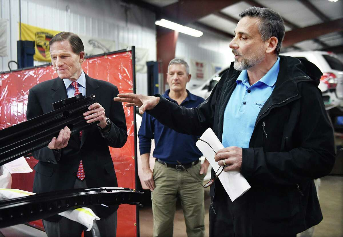 (Catherine Avalone - New Haven Register) Anthony Ferraiolo, President of the Auto Body Association of Connecticut (ABAC) and owner of A & R Body Specialty & Collision Works, Inc. in Wallingford explains the difference between a factory-made part and an imitation to U.S. Senator Richard Blumenthal (D-Conn.) examines an imitation which is sold for $90 less, but inferior to the part made by Ford, Saturday, February 28, 2015. Body shop owners demonstrated the differences in quality and performance between the parts and to remind consumers that they have the right to choose where to repair their vehicles, regardless of recommendations from their auto insurer.