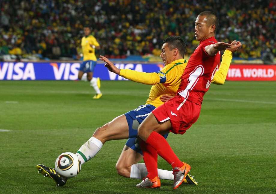 JOHANNESBURG, SOUTH AFRICA - JUNE 15:  Lucio of Brazil tackles Jong Tae-Se of North Korea during the 2010 FIFA World Cup South Africa Group G match between Brazil and North Korea at Ellis Park Stadium on June 15, 2010 in Johannesburg, South Africa.  (Photo by Richard Heathcote/Getty Images) *** Local Caption *** Lucio;Jong Tae-Se Photo: Richard Heathcote, Getty Images / 2010 Getty Images