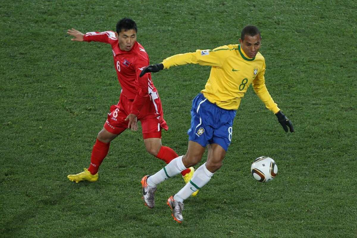 JOHANNESBURG, SOUTH AFRICA - JUNE 15: Kim Kum-Il of North Korea and Gilberto Silva of Brazil in action during the 2010 FIFA World Cup South Africa Group G match between Brazil and North Korea at Ellis Park Stadium on June 15, 2010 in Johannesburg, South Africa. (Photo by Ian Walton/Getty Images) *** Local Caption *** Kim Kum-Il;Gilberto Silva