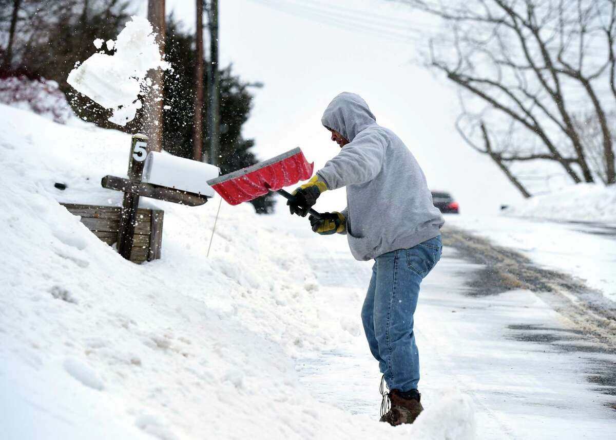 (Arnold Gold-New Haven Register) Shawn Venson of Ansonia shovels snow from a driveway for a friend on Hine St. in Seymour on 2/9/2015.