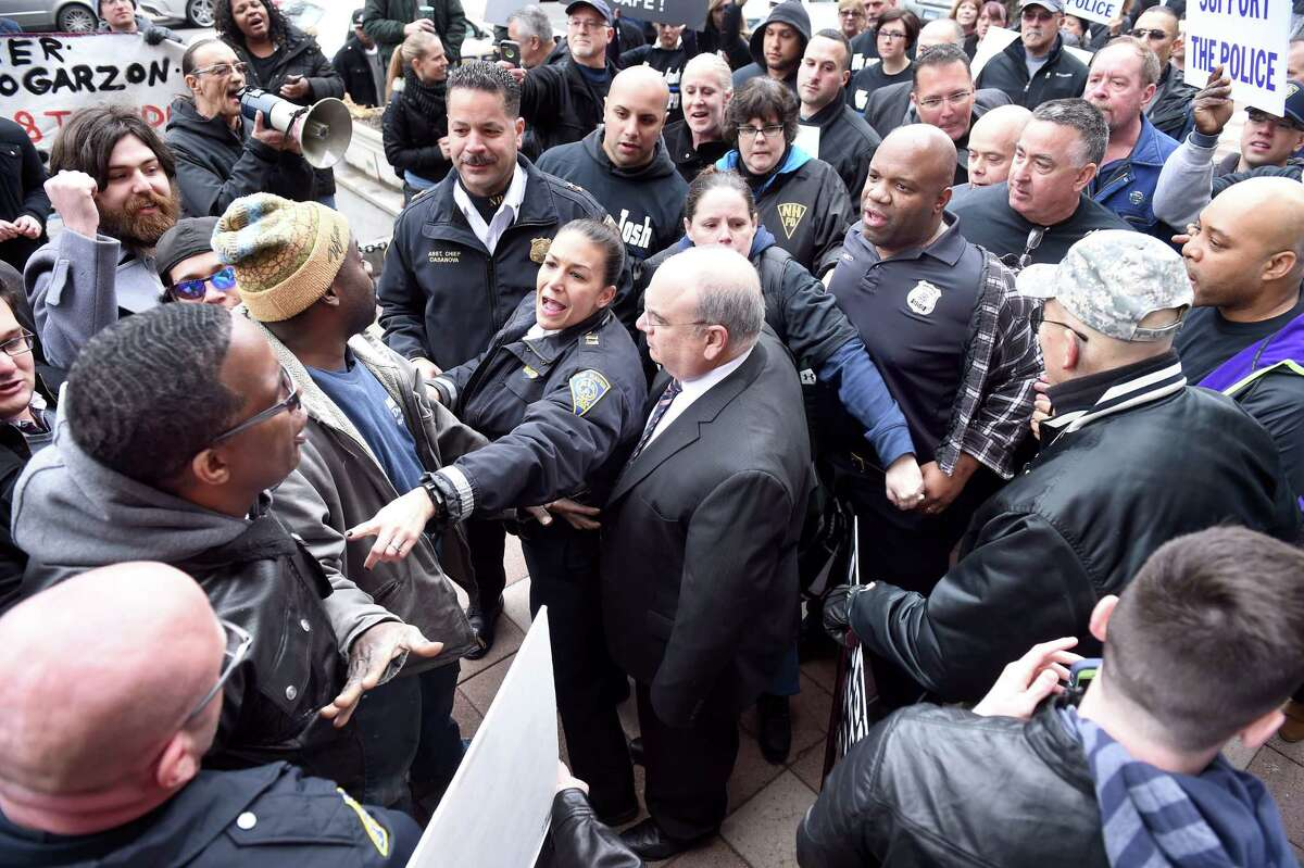 New Haven Police Capt. Julie Johnson (center) helps separate members of a Pro-Police Rally (right)supporting Officer Joshua Smereczynsky from counter protesters in front of City Hall in New Haven on 3/27/2015. Photo by Arnold Gold/New Haven Register agold@newhavenregister.com