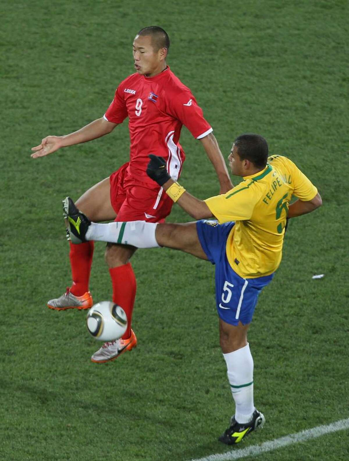 JOHANNESBURG, SOUTH AFRICA - JUNE 15: Jong Tae-Se of North Korea and Felipe Melo of Brazil battle for the ball during the 2010 FIFA World Cup South Africa Group G match between Brazil and North Korea at Ellis Park Stadium on June 15, 2010 in Johannesburg, South Africa. (Photo by Ian Walton/Getty Images) *** Local Caption *** Jong Tae-Se;Felipe Melo of Brazil