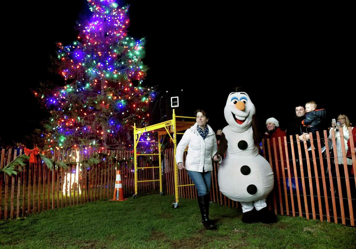 Michelle Call (left) leads Anna Munafo as Olaf during the Christmas tree lighting on the Guilford Green on 12/4/2015. Photo by Arnold Gold/New Haven Register agold@newhavenregister.com
