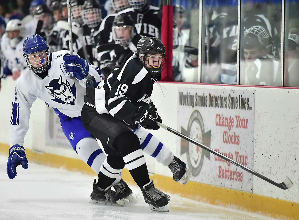 (Catherine Avalone - New Haven Register) Xavier's Jacob Monroe and West Haven's Hunter Cole in pursuit of the puck Wednesday, December 30, 2015, at the West Haven High School Christmas Tournament at the Edward L. Bennett Rink. The Falcons won, 5-2.
