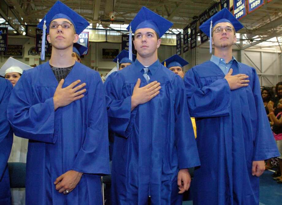 Carlos Aponte, left, Anthony Andress and Peter Adamakos hold their hands over their heart during the Pledge of Allegiance at the Henry Abbott Technical High School graduation at the O'Neill Center on Western Connecticut State University's campus in Danbury, June 15, 2010. Photo: Chris Ware / The News-Times