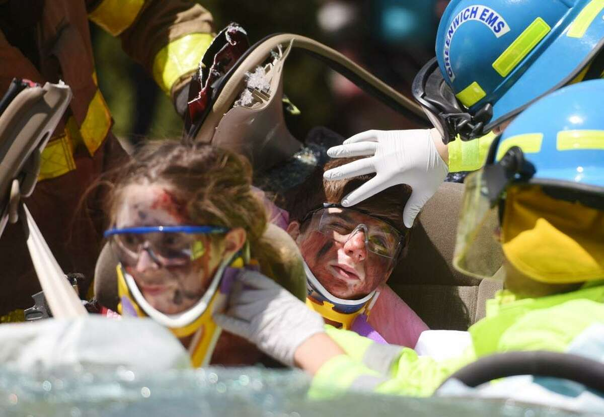 Junior Sara Defazio and sophomore Ezeqiel Konecny are tended to by Greenwich EMS and firefighters during a mock car crash demonstration at the annual Safe Driving Day at Greenwich High School in Greenwich, Conn. Thursday, May 14, 2015. Safe Driving Day activities included a car crash demonstration, car crash riding simulator,