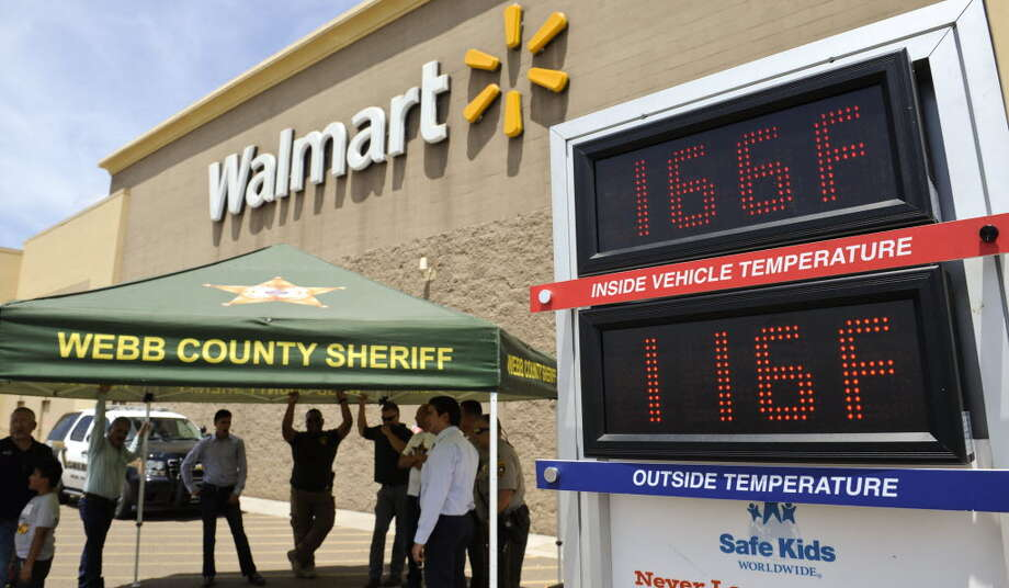 Webb County Sheriff's officers and officials stand under the shade with a Wal-Mart employee and family outside of Wal-Mart on Zapata Highway on Tuesday, August 1, 2017 as a thermometer records the temperatures inside and outside of a Webb County Sheriff's vehicle. Photo: Danny Zaragoza