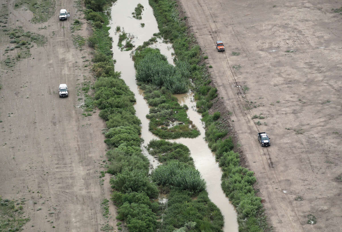 U.S. Border Patrol (left), and Mexican immigration agents perform a joint patrol along the Rio Grande at the U.S.-Mexico border as seen from a U.S. Customs and Border Protection helicopter on August 1, 2017 in El Paso, Texas. Logistical challenges are just some of the complications facing the construction of a border wall proposed by President Trump.
