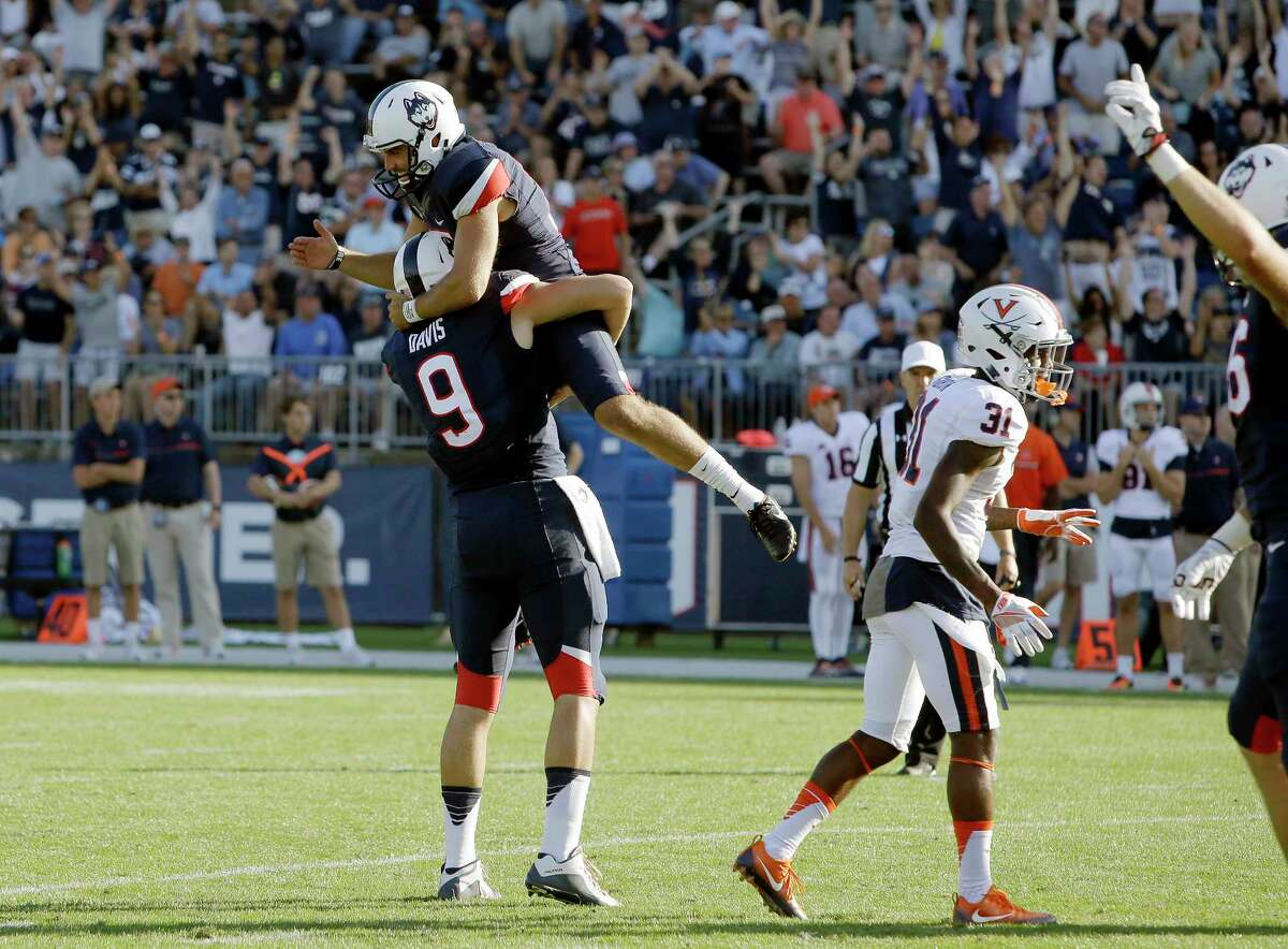 Connecticut placekicker Bobby Puyol, top, celebrates his game-winning field goal with Tyler Davis (9) beside Virginia's Kareem Gibson (31) in the second half of an NCAA college football game at Pratt & Whitney Stadium at Rentschler Field, Saturday, Sept. 17, 2016, in East Hartford, Conn. Connecticut won 13-10.