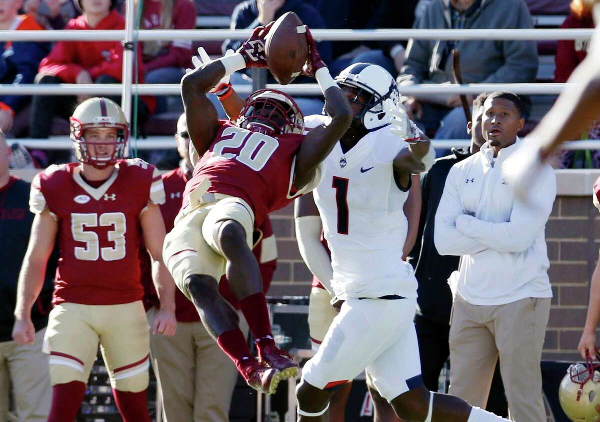 Boston College defensive back Isaac Yiadom (20) can not make the interception in front of Connecticut wide receiver Hergy Mayala (1) during the first half of an NCAA college football game in Boston, Saturday, Nov. 19, 2016.