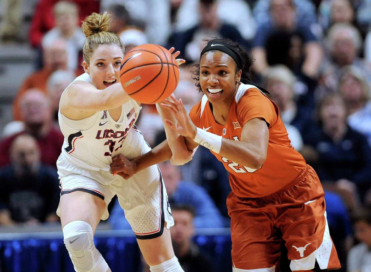 Connecticut's Katie Lou Samuelson, left, and Texas' Brianna Taylor, right, chase down the ball in the first half of an NCAA college basketball game, Sunday, Dec. 4, 2016, in Uncasville, Conn.