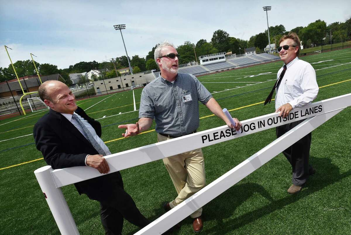 New Haven Public Superintendent of Schools, Garth Harries, Chief Operations Officer, Will Clark, and SLAM Collaborative Design Principal, Glenn Gollenberg, left to right, talk about the seating capacity and additional areas for viewing during a walking tour for the media at the recently restored Bowen Field at Crescent Street in New Haven, , Thursday, July 28, 2016. (Catherine Avalone/New Haven Register)