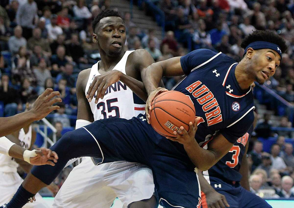 Auburn's Anfernee McLemore (24) fights for a rebound with Connecticut's Amida Brimah (35) during the second half of an NCAA college basketball game in Hartford, Conn., on Friday, Dec. 23, 2016.