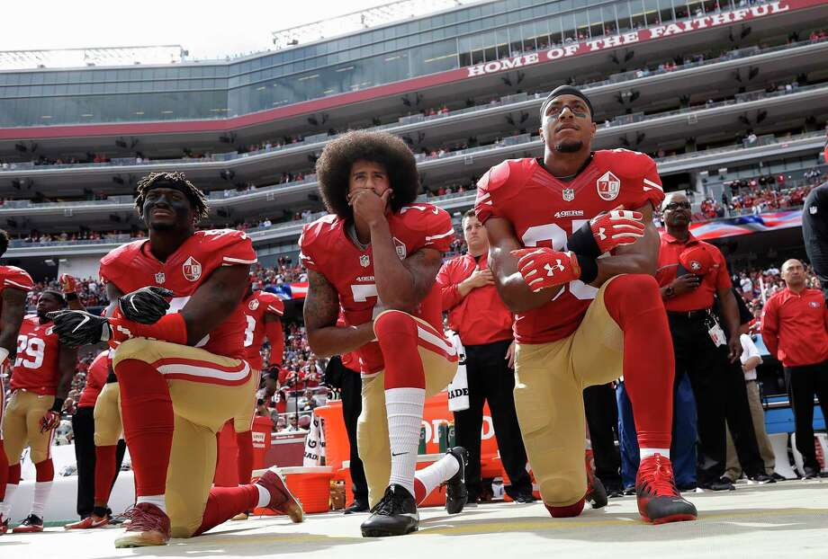 San Francisco 49ers outside linebacker Eli Harold, left, quarterback Colin Kaepernick, center, and safety Eric Reid kneel during the national anthem before an NFL football game against the Dallas Cowboys in Santa Clara, Calif., on Oct. 2, 2016. Photo: Marcio Jose Sanchez, AP / Copyright 2016 The Associated Press. All rights reserved.