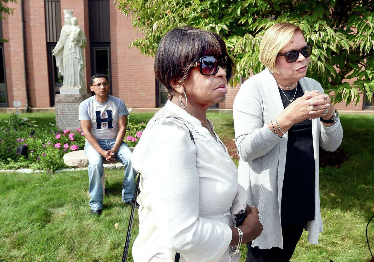 Left to right, Lauro Barranco of New Haven, Ana Torres of Hamden and Griselle Malavet of Hamden wait for a bus in the parking lot of Our Lady of Pompeii Church in East Haven for a trip to Philadelphia and the World Meeting of Families on 9/25/2015. Photo by Arnold Gold/New Haven Register agold@newhavenregister.com