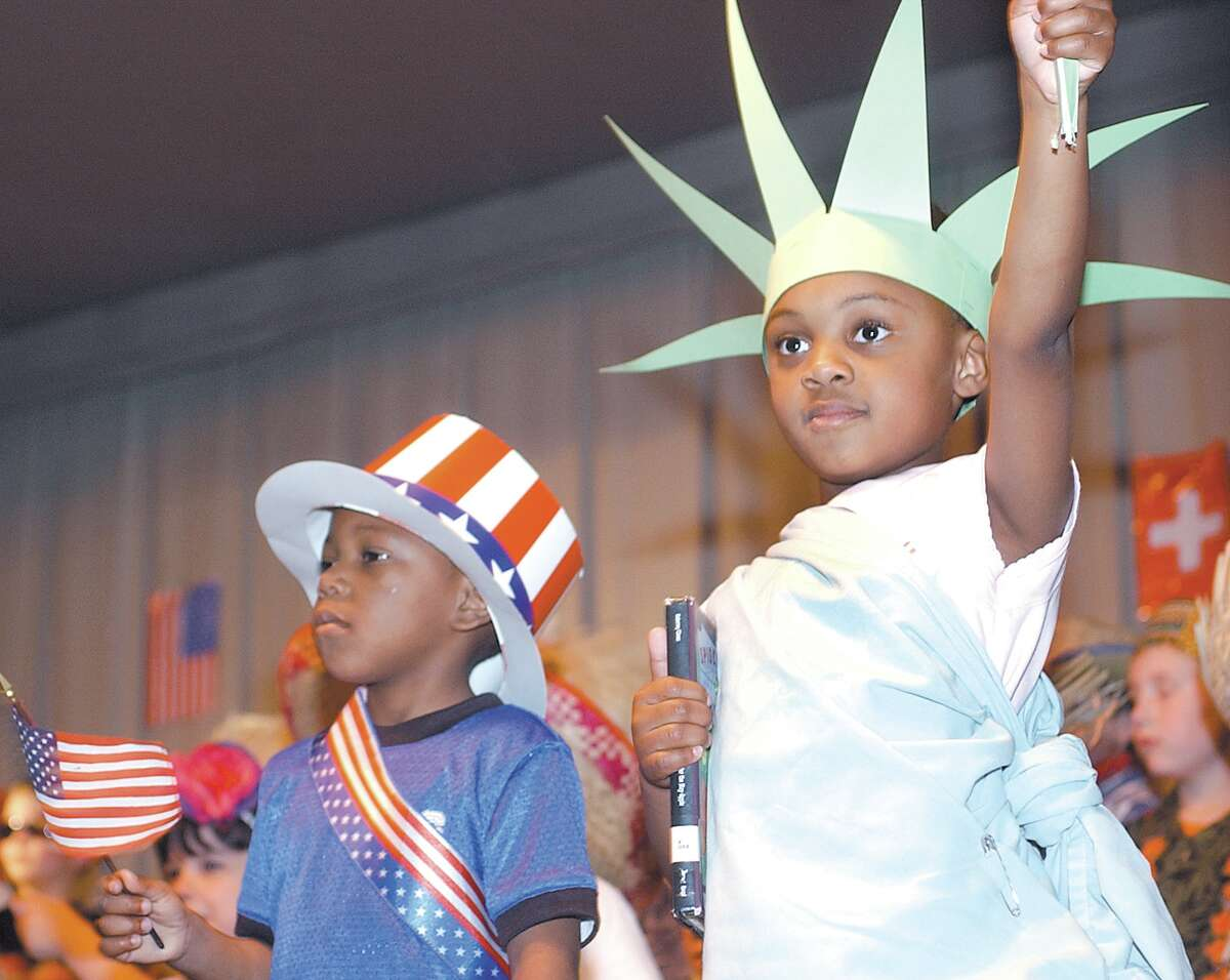 Kayla McGill is dressed as the Statue of Liberty and Jordan Baker as Uncle Sam as they perform for an audience of students' family and friends with fellow kindergarteners at MacDonough School in Middletown Tuesday morning. The students' performances celebrated different cultures including those of Mexico, Japan, Jamaica, France and the USA........photo by Irena Pastorello.......051303.irenaphoto.....web:MPamer.jpg