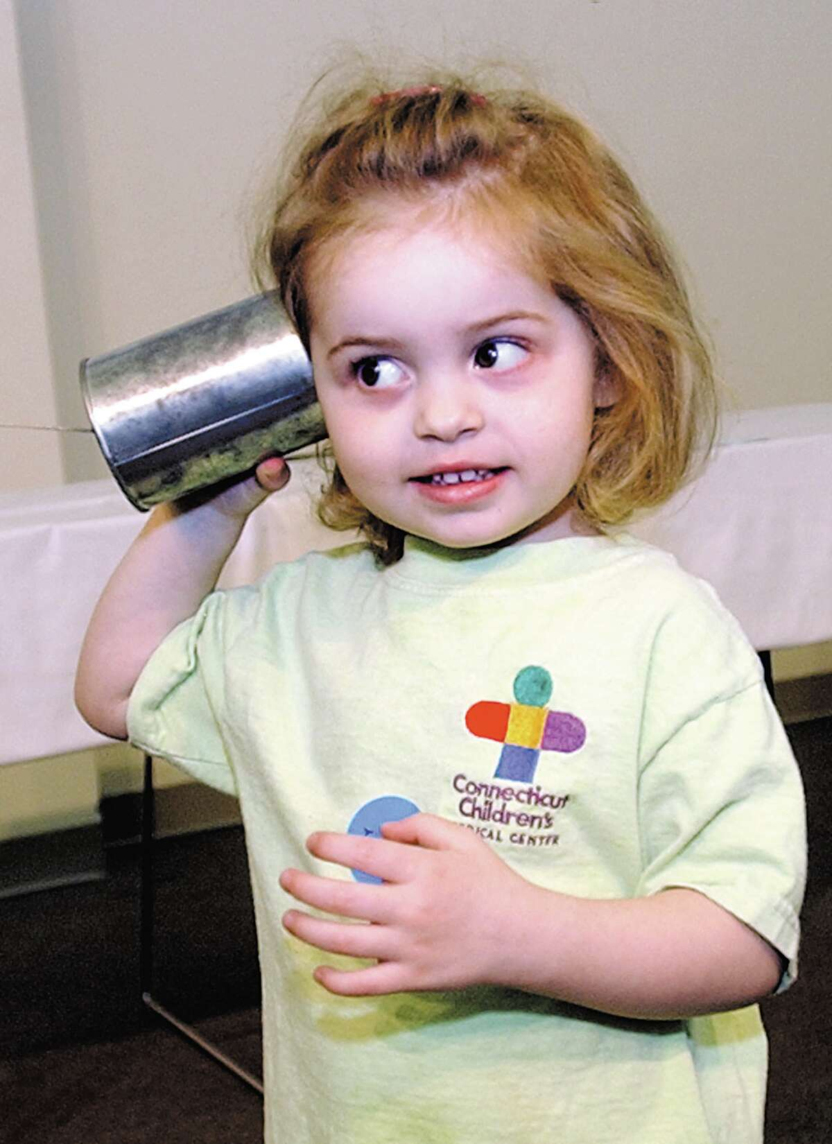 Florence Petite, 4, listens for the voice of her father Darren of Bloomfield at the Vintage Radio and Communications booth at the Home Education Fair at Middlesex Community College on Saturday..............TW photo.............053103............MPtalk.jpg