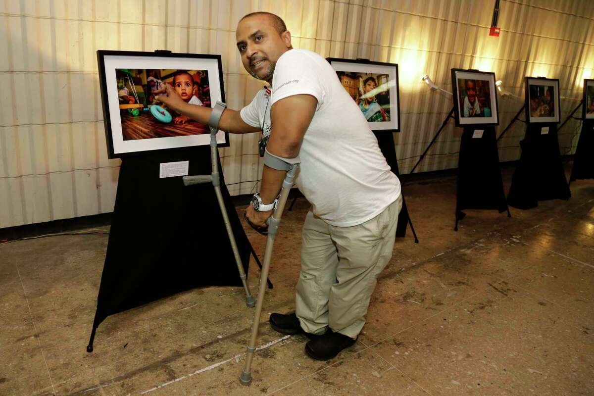 In this Aug. 27, 2016 photo, Gautam Lewis talks about an image displayed at his photography exhibition in connection with Mother Teresa's canonization in Kolkata, India. For Lewis, a polio victim abandoned by his parents as a child and rescued by Mother Teresa, the nun is already a saint. At seven, he was adopted from an orphanage run by the Missionaries of Charity, the order set up by Mother Teresa, and moved first to New Zealand and later England. Lewis, 39, now runs a flying school for people with disabilities in the United Kingdom.