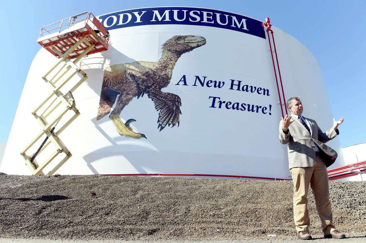 David Skelly, director of the Yale Peabody Museum of Natural History, speaks during a ceremony showcasing a mural of the dinosaur, Deinonychus, being installed on a 90,000 barrel heating oil tank at Magellan Midstream Partners, Inc., at New Haven Harbor on 9/13/2016. The mural designed by Bayla Arietta of New Haven is being applied in sections by Juan Treannes and Shawn Martel of Merritt Graphics. The material is 3M performance vinyl panels. Photo by Arnold Gold/New Haven Register agold@newhavenregister.com