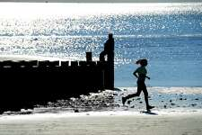 (Peter Hvizdak - New Haven Register) Enjoying pleasant weather together along the Shoreline, Pam Burchell of New London watches her granddaughter Kylie Sevigny of Lyme, 10, run along the Old Saybrook Town Beach Friday afternoon, October 14, 2016.