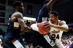 Cincinnati's Kyle Washington (24) looks to pass around Connecticut's Amida Brimah, center, and Kentan Facey, left, in the first half of an NCAA college basketball game, Saturday, Feb. 4, 2017, in Cincinnati.