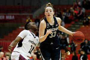 Connecticut's Katie Lou Samuelson (33) drives past Cincinnati's Shanice Johnson (21) during the first half of an NCAA college basketball game Tuesday, Feb. 7, 2017, in Cincinnati.
