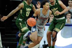 Connecticut's Jalen Adams, center, is guarded by South Florida's Geno Thorpe, and Troy Holston, right, during the first half of an NCAA college basketball game, Wednesday, Feb. 8, 2017, in Storrs, Conn.