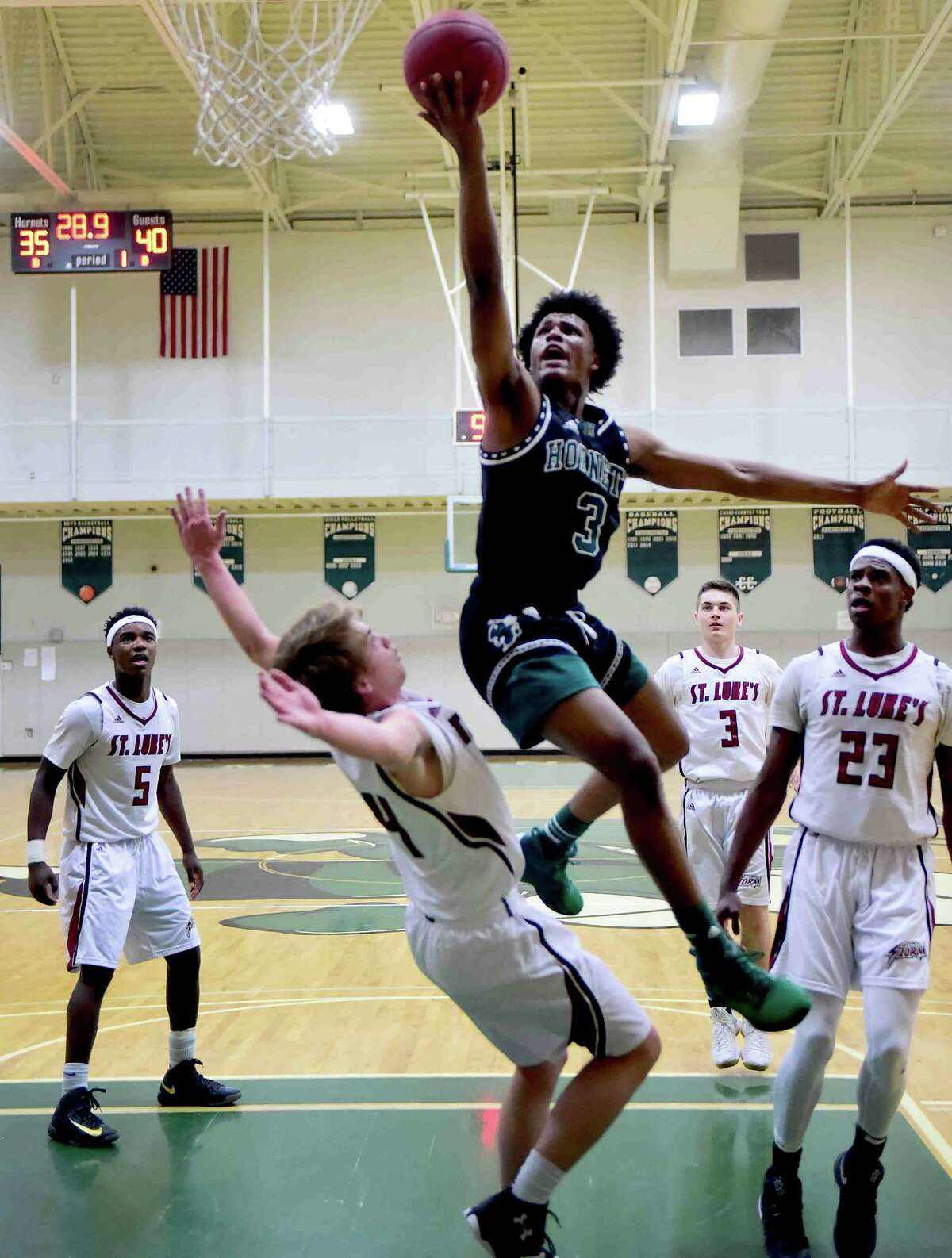 (Peter Hvizdak - New Haven Register) John Wisdom of St. Luke's of New Canaan gets a charge call, left, against TJ Rountree (CQ) of Hamden Hall, right, basketball during first half basketball at Hamden Hall Monday, December 12, 2016,