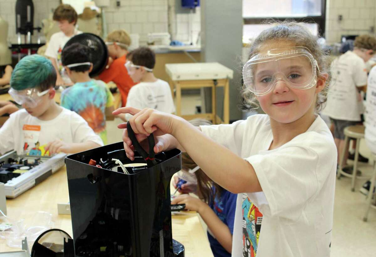Maryn Brooks, 7, takes apart a coffee maker to build something new at Camp Invention in Wilton on Tuesday, Aug. 1, 2017.