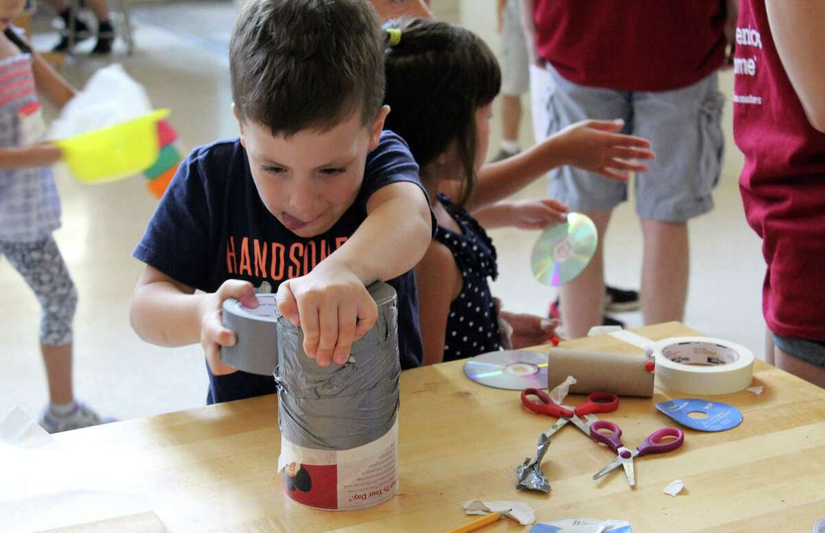 Christopher Rainone uses duct tape to create an invention at Camp Invention in Wilton on Tuesday, Aug. 1, 2017.