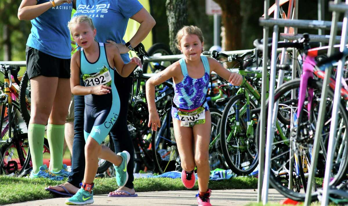 Annabelle Sager, 8, from left, and Kenady Hilliard, 9, both of Cypress, make their way to the run course during the Cypress Youth Triathlon at the Lakeland Activity Center in Cypress on July 29, 2017. (Photo by Jerry Baker/Freelance)