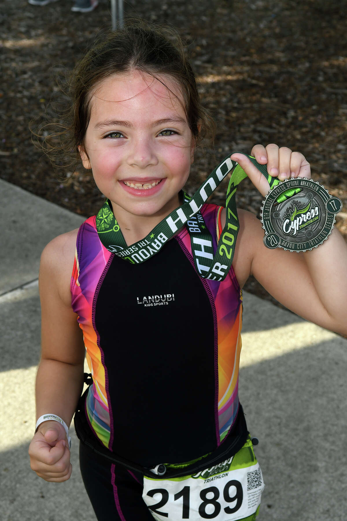 Louise Galo, 7, of Cypress and a 2nd grader at Wells Elem., shows off her medal after completing the Cypress Youth Triathlon at the Lakeland Activity Center in Cypress on July 29, 2017. (Photo by Jerry Baker/Freelance)