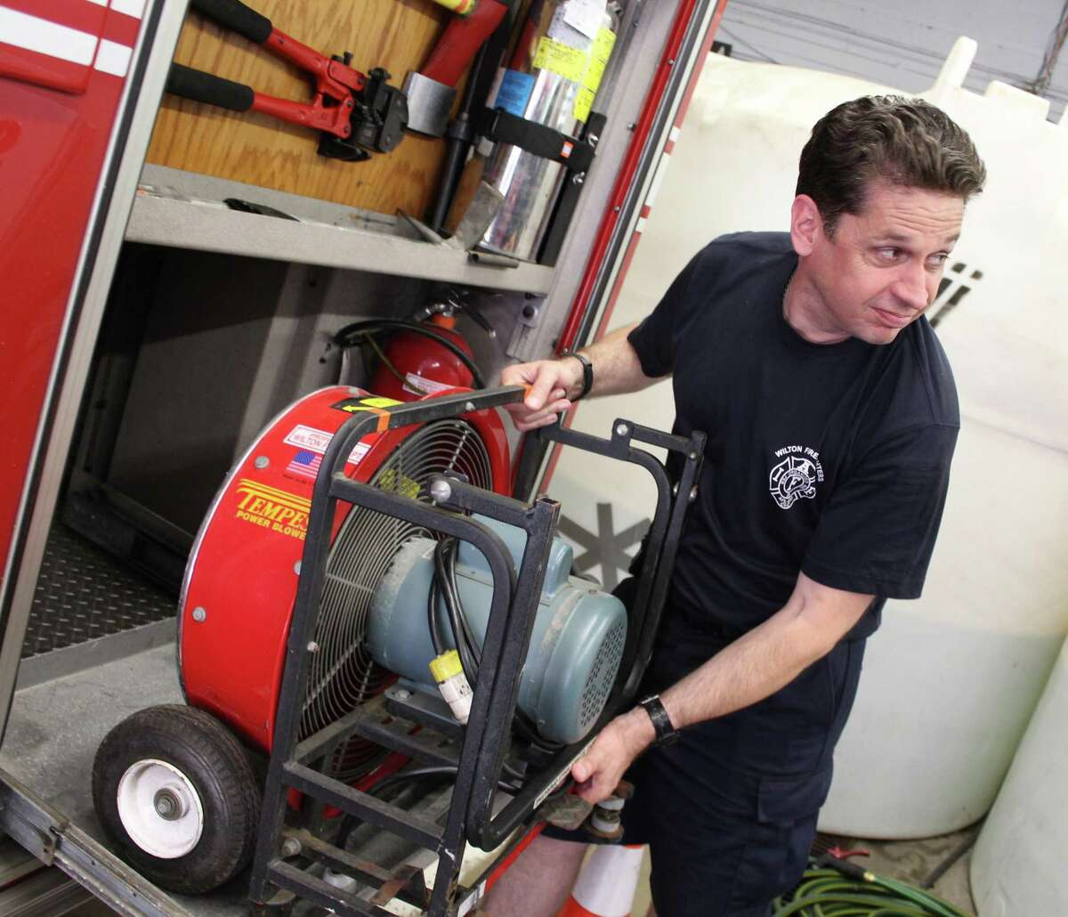 Bryan Montgomery, a five-year veteran of the Wilton Fire Department, checks a fire truck's inventory during the morning shift at Fire House 2 in North Wilton.