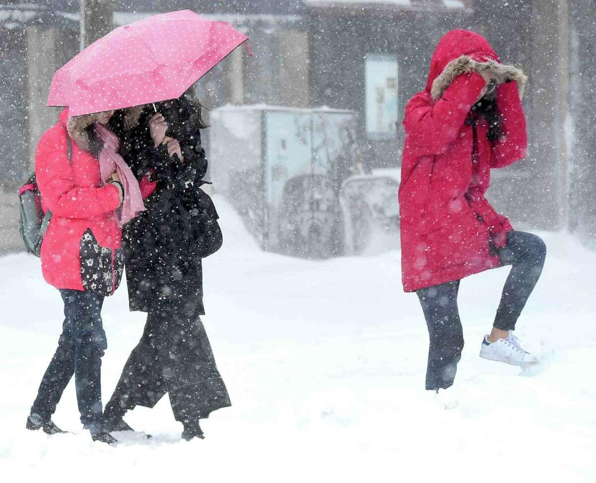 (Peter Hvizdak - New Haven Register) Pedestrians braving the Nor'easter snow storm cross Chapel Street to York Street in New Haven Thursday, February 9, 2017.
